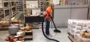 Water Damage Restoration Technician Cleaning After Warehouse Flooding